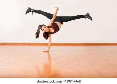 Beautiful female jazz dancer doing a one hand stand and a leg split in the air and smiling in a dance studio