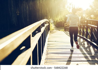 Beautiful female jogger running during sunset across bridge