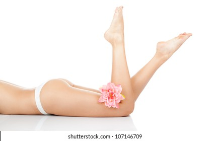 Beautiful female legs, ass back body isolated over white background. lying on the floor white panties pink flower long leg, Beauty spa and skin care concept.