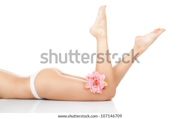 Schöne weibliche Beine, Hinterkörper einzeln auf weißem Hintergrund. Das Hotel liegt auf dem Boden, die weißen Pantoletten, das rosafarbene, lange Bein, das Beauty Spa und das Hautpflegekonzept.