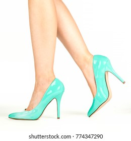 Beautiful female legs in classic pump high heels shoes made of turquoise patent leather. XXL image