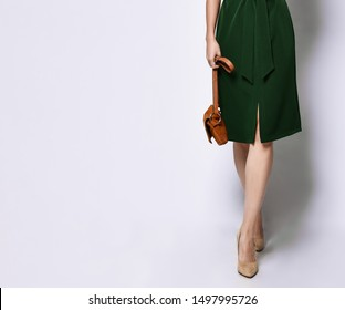 Beautiful female legs in high-heeled shoes in a green dress from the designer and brown women's handbag on a white background.
