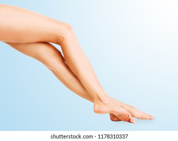 Beautiful female legs isolated on the blue background