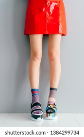 Beautiful female legs in mismatched trendy socks standing in two different fashionable high wedge leather sandals on white surface. Odd young girl in red skirt wearing high sole summer stylish shoes
