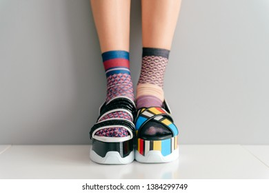 Beautiful female legs in mismatched trendy socks standing in two different fashionable high wedge leather sandals on white surface. Odd disargonized  young girl wearing high sole summer stylish shoes