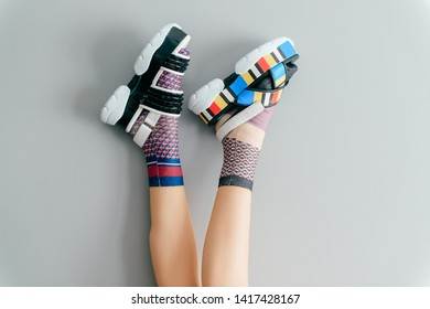 Beautiful female legs in mismatched trendy socks posing in two different fashionable high wedge leather sandals on gray background. Odd disargonized young girl wearing high sole summer stylish shoes
