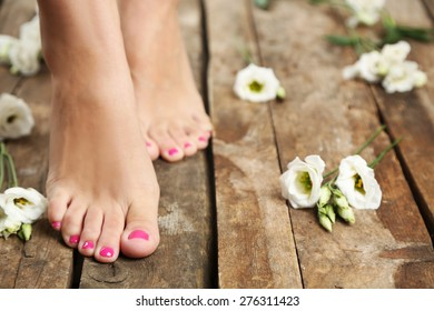 Beautiful female legs on rustic wooden floor background