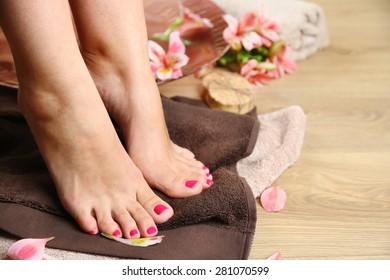 Beautiful female legs on  towel, on wooden floor background