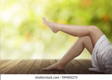 Beautiful female legs on wooden floor over blur background