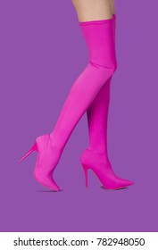 Beautiful female legs in pink stretchy high heels shoes in stockings style against a lilac background.