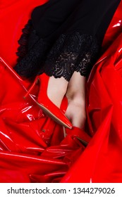 Beautiful female legs in red shoes and black dress with lace on the background of latex red fabric. Conceptual, advertising and commercial design. Copy space.