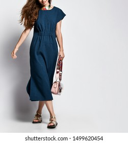 Beautiful female legs in summer sandal shoes in a blue long dress from the designer and a women's handbag on a white background.