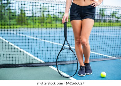 Beautiful female legs with tennis racket on tennis blue court