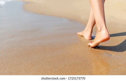 Beautiful female legs walk on the sea sand.