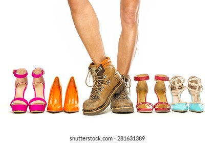 Beautiful female legs wearing mens working boots in vintage design and standing in a group of fashionable high heels shoes.