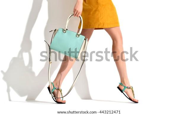 茶色の黄色いデザイナーのドレスに夏の靴をはいた美しい女性の脚と白い背景に青いミント女性のクラッチバッグ