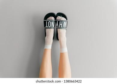 Beautiful female legs in white mesh teen socks wearing fashionable rubber slippers with inscroption why noton gray background. Elegant stylish trendy leg-wear . Voguish legwear for fashionable ladies
