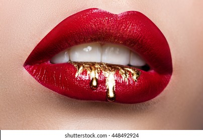 Beautiful female lips closeup. Red lipstick, gold paint flowing over his lips. Stock Photo Cosmetic Advertising