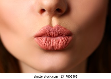 Beautiful female lips making kiss gesture flirting to camera closeup. Young pretty sexy girl facial oral botox body part hollywood smiling portrait