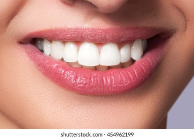 Beautiful female lips with shiny lipgloss make-up. Lips care and visage. Snow-white smile