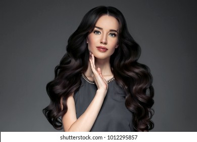 Beautiful female with long brunette hair salon curly and healthy, perfect beuty makeup, young spa model fashion portrait