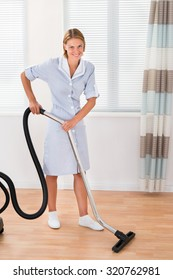 Beautiful Female Maid Cleaning Wooden Floor With Vacuum Cleaner