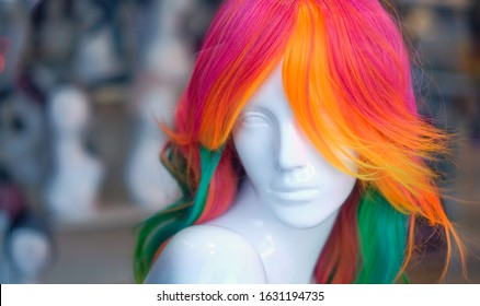 A beautiful female mannequin head with perfect pale skin and rainbow coloured long hair.