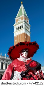 Beautiful female mask in Venice carnival with bell tower in San Marco square.