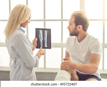 Beautiful female medical doctor is talking to handsome patient with broken leg and showing him X-ray picture on tablet