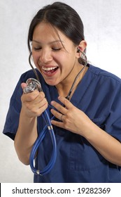 A beautiful female medical healthcare doctor or nurse wearing a stethoscope and being playful.