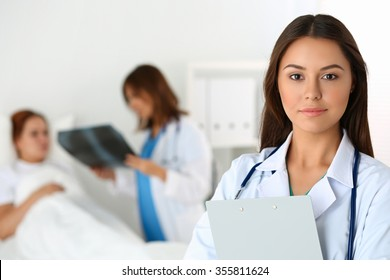 Beautiful female medicine doctor looking in camera in front of patient lying in bed and communicating with traumatologist. Radiology or traumatology medical concept. Medical care or insurance concept