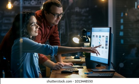 Beautiful Female Mobile Gaming Application Developer Talks With Her Male Colleague, They Discuss Creative Design. Stylishly Lit Office.