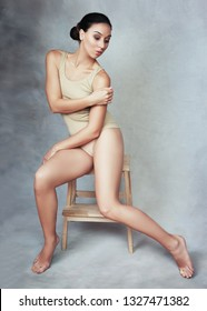 beautiful female model in beige swimsuit posing at studio