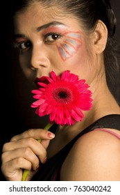 beautiful female model in a black top and red flowers and roses in front of a black background