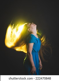 Beautiful female model in blue dress posing at studio in the light flashes on black background. Attractive cute girl with long sun-drenched blowing and  flying flaming hair.