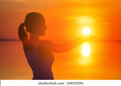 Beautiful female model enjoying sunset and touch sun by both hands at seaside. Calm water of salt lake Elton reflects silhouette of woman. Sun goes under horizon. Girl stands alone in water.