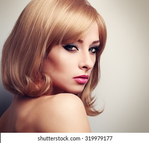 Beautiful female model with fashion blond hairstyle and green eyes looking sexy. Closeup toned portrait