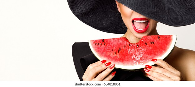 Beautiful female model with perfect face and red hat holding a watermelon at her face