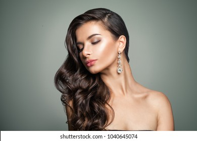 Beautiful Female Model. Perfect Makeup. Wavy Hair. Jewelry Earrings