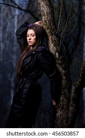 Beautiful female model posing in the dark forest