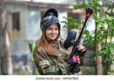 Beautiful female model posing in paintball ammunition outdoors