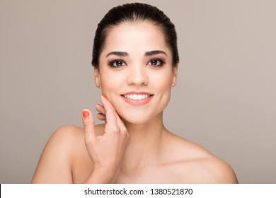 Beautiful female model touching her smooth face over colored background