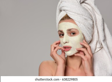 Beautiful female model with towel on her hear and white facial cosmetic mask on her face. Beauty cosmetic concept. Isolated on gray background.