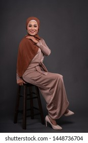 """Beautiful female model wearing """"baju kurung"""" dress with hijab, a modern lifestyle outfit for Muslim woman isolated over grey background. Stylish Muslim female hijab fashion lifestyle concept."""