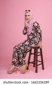 "Beautiful female model wearing batik design ""baju kurung"" with  hijab, sitting in various poses isolated over pink background. Eidul fitri fashion and beauty concept."