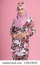 "Beautiful female model wearing batik design ""baju kurung"" with hijab, a modern lifestyle outfit  for Muslim woman isolated over pink background. Eidul fitri fashion and beauty concept."