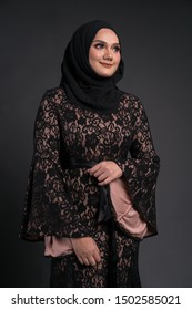 """Beautiful female model wearing black color """"baju kurung"""" dress with hijab, a modern lifestyle outfit for Muslim woman,  isolated over grey background. Muslim female hijab fashion lifestyle concept."""