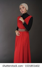 Beautiful female model wearing black inner and red dress with hijab, a modern lifestyle outfit  for Muslim woman isolated over grey background. Stylish hijab fashion lifestyle portraiture concept.