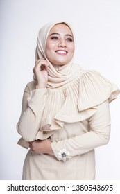 """Beautiful female model wearing bright color """"baju kurung"""" dress with hijab, a modern lifestyle outfit  for Muslim woman isolated over white background. Eidul fitri fashion and beauty concept."""