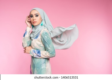 """Beautiful female model wearing bright color """"baju kurung"""" dress with hijab, a modern lifestyle outfit  for Muslim woman isolated over pink background. Eidul fitri fashion and beauty concept."""